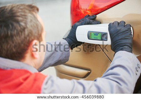 colourist man selecting color of car with paint matching scanner - stock photo