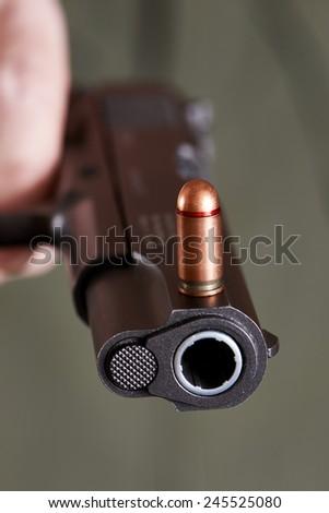 Colt gun and cartridge on khaki color background - stock photo