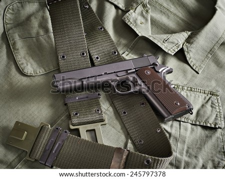 Colt gun pistol and belt lie on military jacket closeup - stock photo