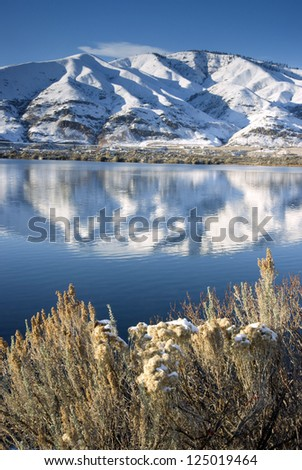 Columbia River Flows After Fresh Snow beneath Mountain Peaks and Homesteads - stock photo