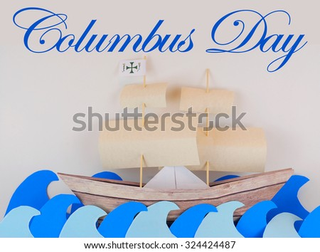 Columbus Day image with paper cutout and folded ship, sails and ocean on a light background. Shadows present to emphasize 3D nature of paper elements. Blue ocean, wooden boat, parchment sails. Cute.