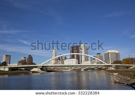 Columbus Ohio along the Scioto river with the Main Street Bridge in the foreground. - stock photo