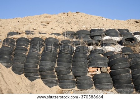 Column stack of old used car tires used to strengthen the earth - stock photo