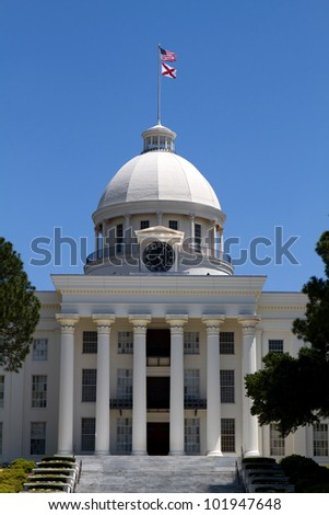 Columned entrance of the Alabama State Capital and dome in Montgomery, Alabama, USA, against a blue sky. - stock photo