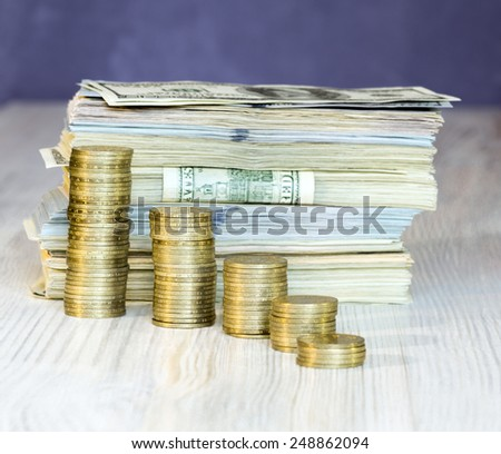 Columns build off coins with large stack of paper currency on the background - stock photo