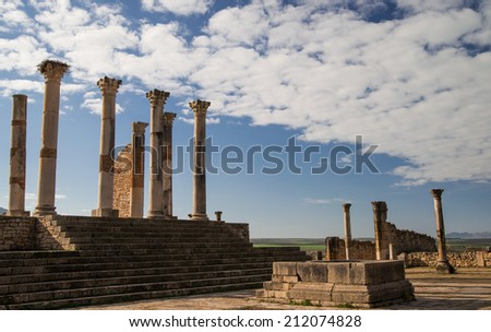 Columns of Roman ruins in Morocco with white clouds and lovely blue sky in the background - stock photo
