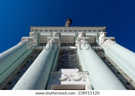Columns of turquoise architectural building in classic style with sculpture of bull on background of blue sky - stock photo