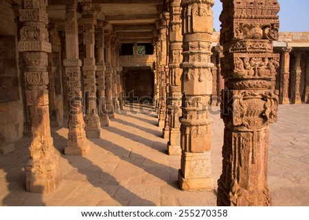 Columns with stone carving in courtyard of Quwwat-Ul-Islam mosque, Qutub Minar complex, Delhi, India - stock photo