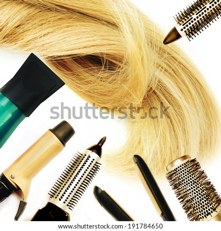 Comb brushes and hairdryer with blond hair. - stock photo