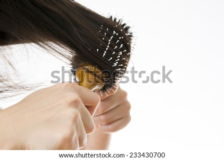 Comb in a female hand on a white background. Combing her hair.