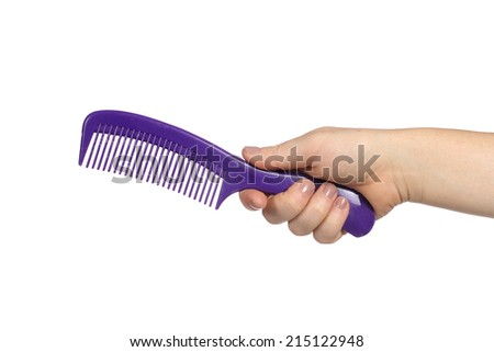 Comb in hand on a white background - stock photo