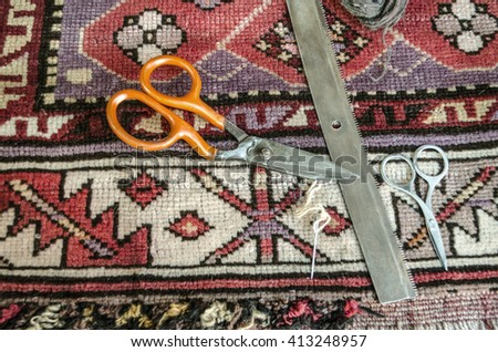 Comb,scissors,needle and woolen thread for the restoration of the old  woolen carpet