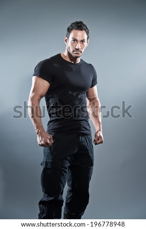 Combat muscled fitness man wearing black shirt and pants. Studio shot against grey. - stock photo