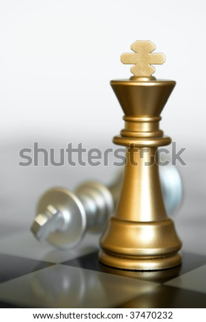 Combination from chessmen on an old board. Focus on black king. - stock photo