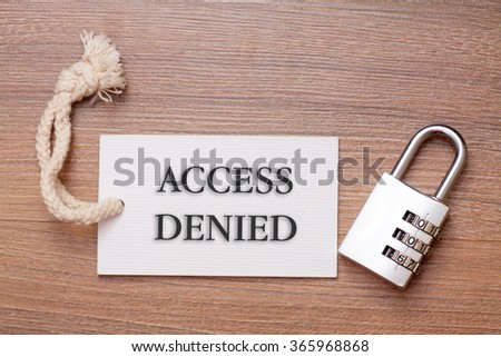 Combination number padlock on wood background with access denied written on label tag - stock photo