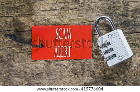 Combination number padlock on wood background with Scam Alert written on label tag - stock photo