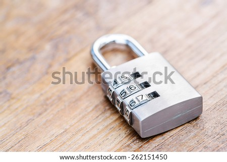 Combination padlock close up with chrome numbers on wooden background
