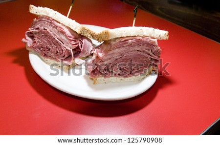 combination tongue corned beef sandwich on seeded rye bread at Jewish deli New York City - stock photo