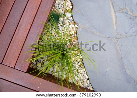 Combinations of plants, timber decking, paving and rocks - stock photo
