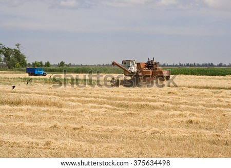 Combine and truck in field.