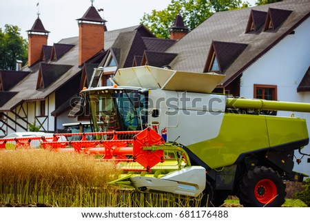 Combine harvester in action on the field. Tractor and harvester at harvest time. The agricultural sector