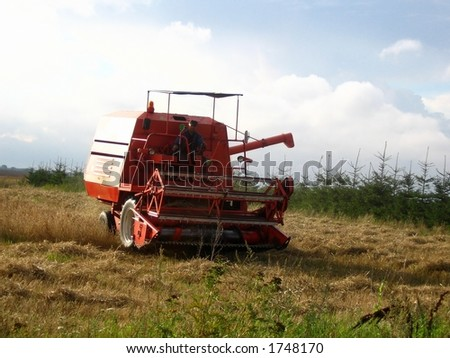 Combine harvester mow cereal. Harvest finishing. All logos have been removed.