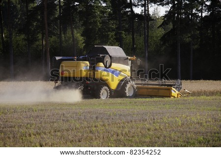 combine harvester with biult-in tractor, harvesting wheat. trademarks removed.