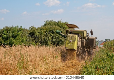 combine harvester working on a oat field - stock photo