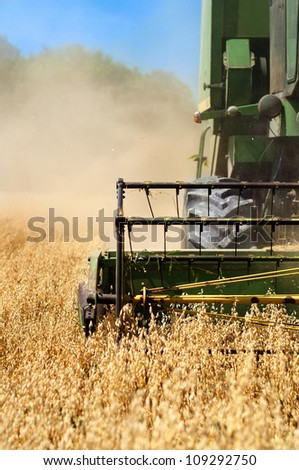 Combine harvesting machinery collecting wheat from the fields - stock photo