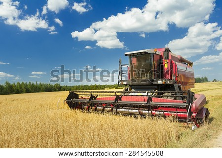 Combine machine with air-conditioned cab is harvesting oats on farm field - stock photo