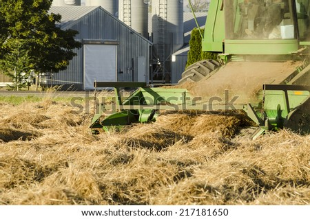Combine working a newly cut field of summer wheat in the Willamette Valley of Oregon - stock photo