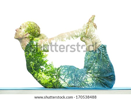 Combining nature with spiritual yoga in a creative portrait of a young woman lying with her body arched holding her toes and her eyes closed in serenity, superimposed with the foliage of trees - stock photo