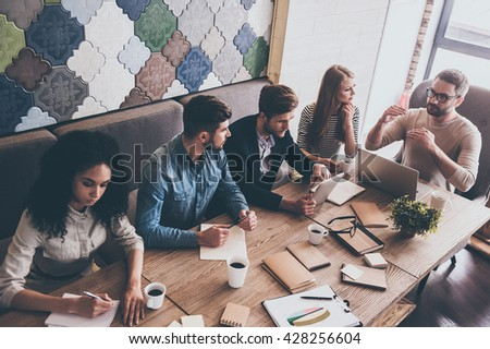 Combining their expertise. Top view of young handsome man in glasses gesturing and discussing something with his coworkers while sitting at the office table - stock photo