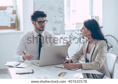 Combining their expertise. Young handsome man in glasses gesturing and discussing something with his beautiful coworker while sitting at the office table - stock photo