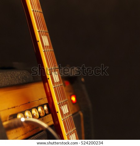 Combo amplifier for electric guitar with guitar neck on the black background. Shallow depth of field, low key, close up. Focus on neck.