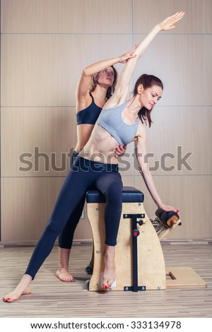 combo wunda pilates chair woman with instructor fitness yoga gym exercise - stock photo