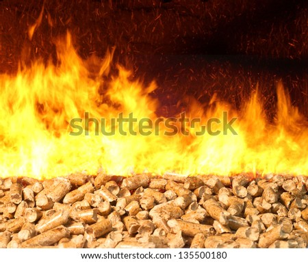 Combustion of biomass pellets with bright fire and flames - stock photo