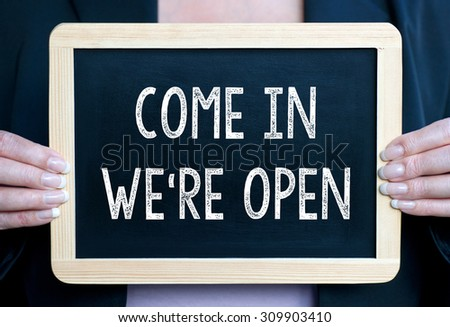 Come in we are open - Businesswoman with blackboard and text