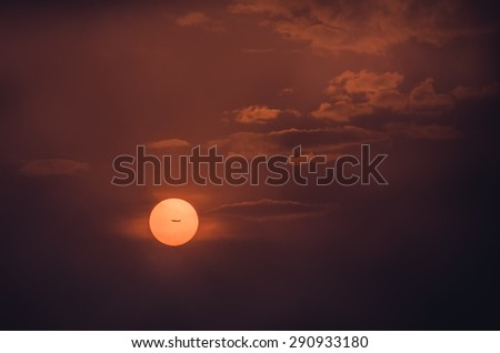 Comercial airplane passing by the center of the Sun at sunset - stock photo