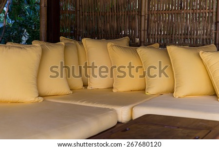comfort, leisure and interior decoration concept - couch with pillows at hotel terrace - stock photo