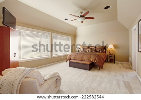 Comfort master bedroom interior with high vaulted ceiling. Beautiful queen size bed in brown color - stock photo