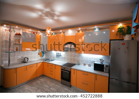 Comfortable apartment in the orange and blue tones. Kitchen with dining room. interior, flat, design, architectural design, style, color, oran, suspended ceilings, floor tiles - stock photo
