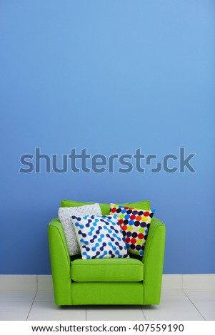 Comfortable armchair with pillows against blue wall background - stock photo