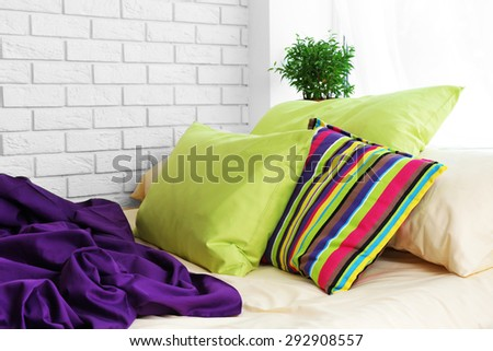 Comfortable bed with colorful pillows and purple blanket in bedroom
