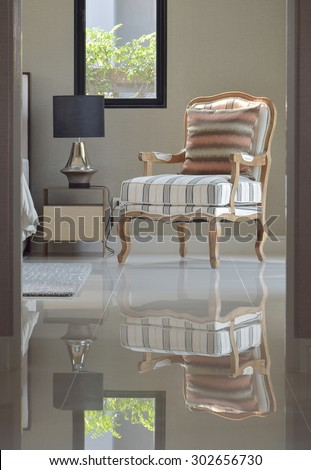 comfortable classic style lounge chair next to the bedside table in bedroom interior - stock photo