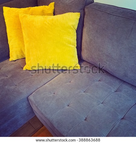 Comfortable corner sofa decorated with two bright yellow cushions. - stock photo