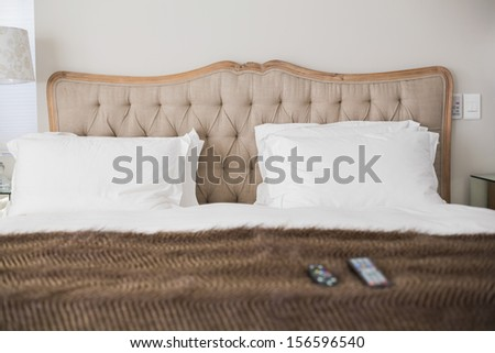 Comfortable double bed with a brown blanket in an hotel room - stock photo
