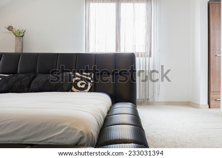 Comfortable double bed with brown elegant headrest - stock photo