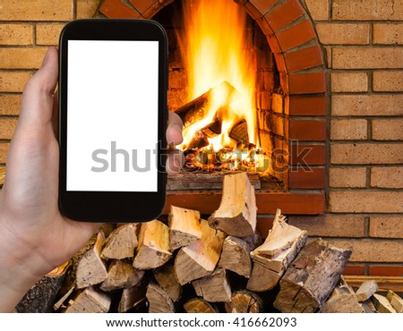 comfortable holiday concept - tourist photographs fireplace on smartphone with cut out screen with blank place for advertising