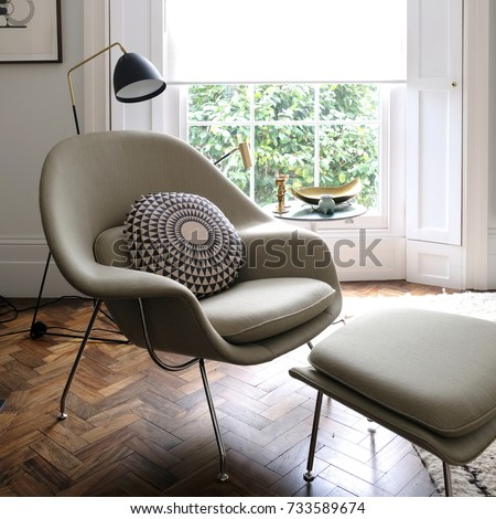 comfortable light green armchair in cosy setting with cushion on dark wood floor in front of